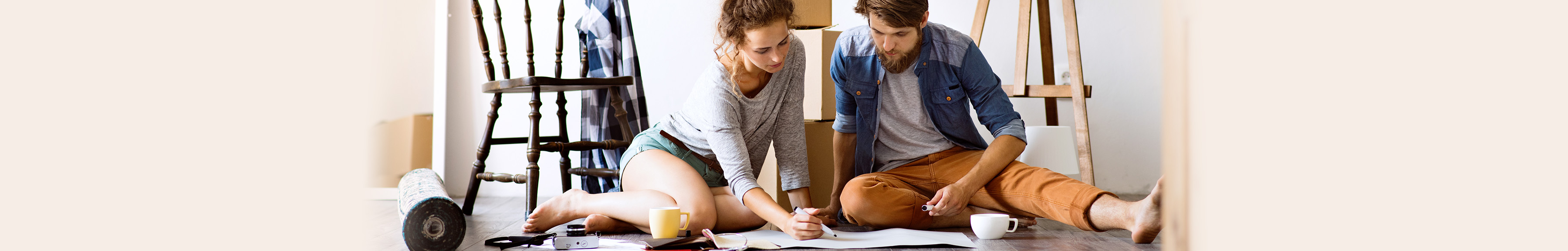 Couple sitting on floor in apartment with moving boxes